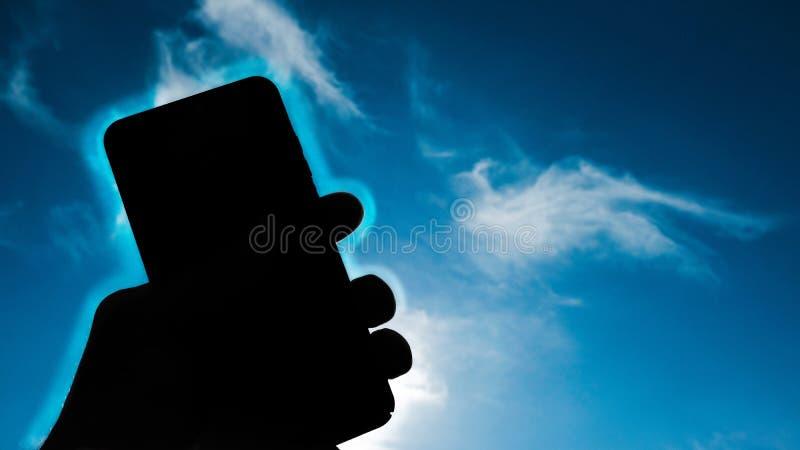 在天空蔚蓝背景,电话辐射概念的人的手藏品智能手机 免版税图库摄影