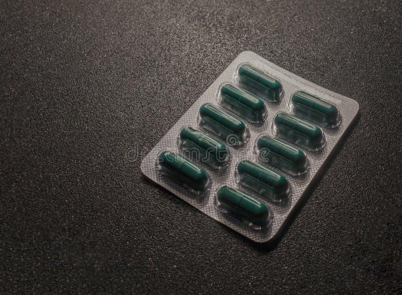 在天线罩包装的绿色药片塑料表面上 图库摄影