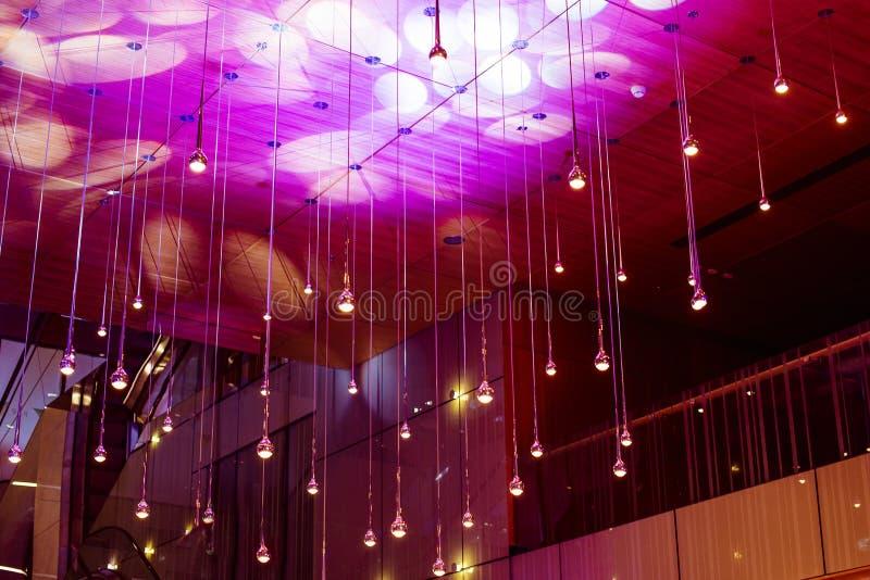 在天花板下的许多圆的灯 在黑暗的时兴的内部的辉光灯 白色或轻的灯在黑暗色的背景发光 免版税库存照片