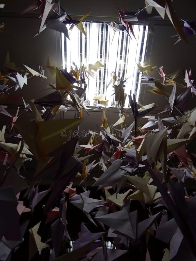 在天花板串的手工制造色的origami起重机 免版税库存照片