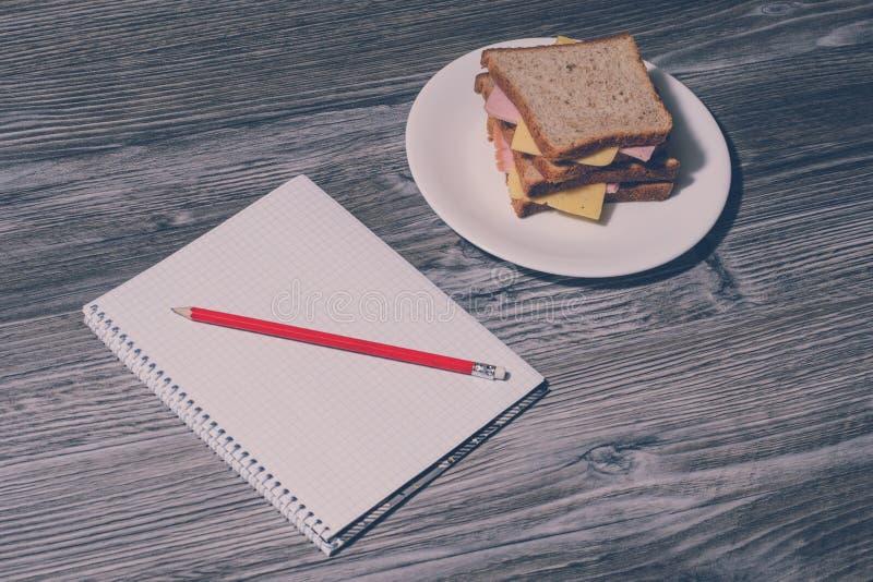 在天花板关闭上的上面午餐看法照片在工作 在笔记本和铅笔,在回合的鲜美乳酪三明治的垂直的看法 图库摄影