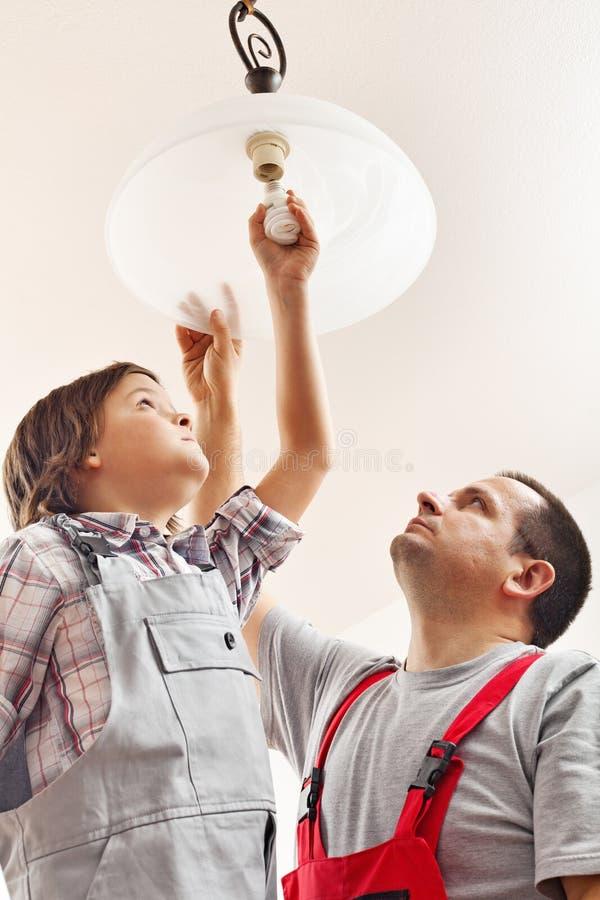 在天花板灯的父亲和儿子改变的电灯泡 免版税库存照片