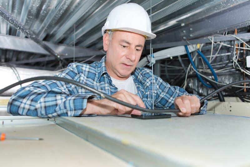 在天花板的成熟电工定象接线 库存照片