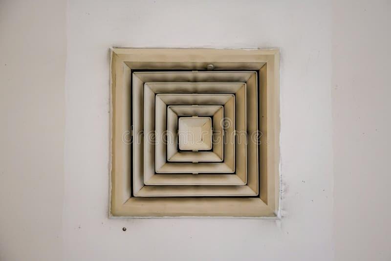在天花板的老和肮脏的空气管道通风孔爱好者在大厦通风系统 库存照片