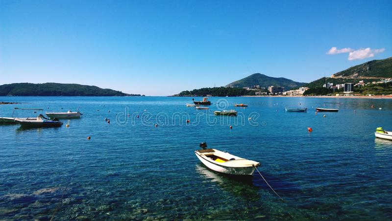 在天蓝色的水的小渔船在布德瓦的中心,在黑山 库存照片