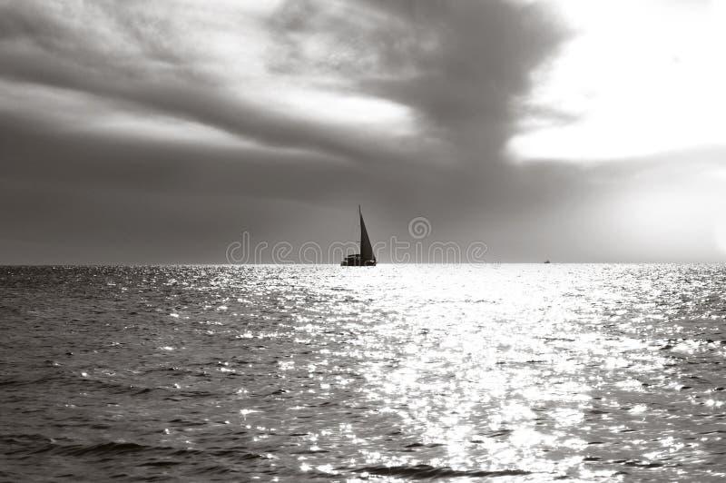 在天际和海光滑的表面的偏僻的帆船在太阳射线  免版税图库摄影