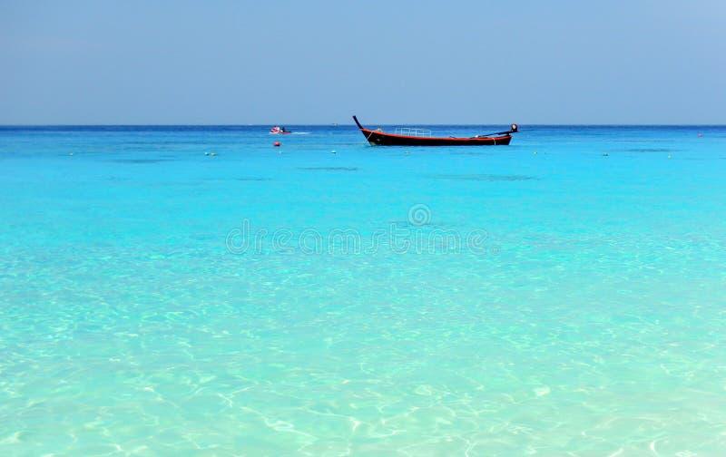 在天际的一条小船在Similan海岛的美丽的绿松石水域中,酸值, Similan,攀牙府,泰国 库存图片