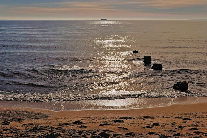 在天际的小船,与岩石,沙滩和太阳光芒反射了到地中海,palma,马略卡,西班牙 库存图片