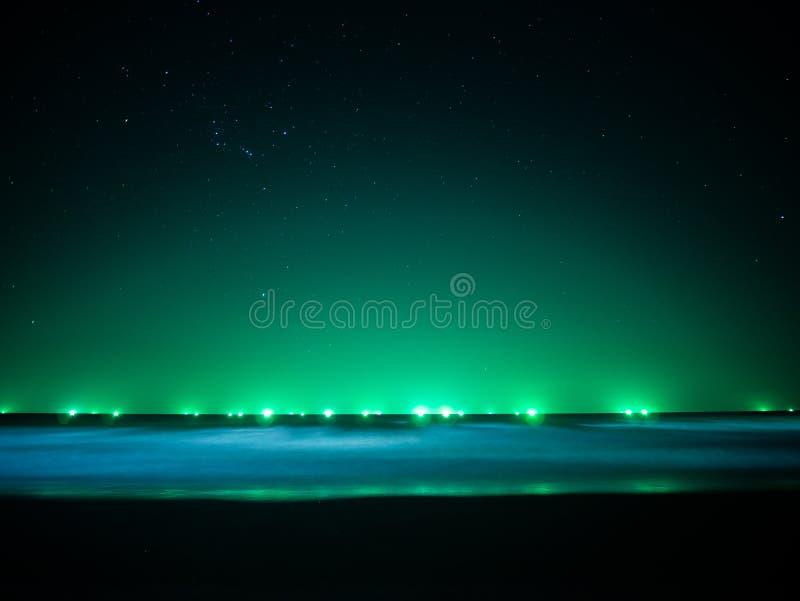 在天际线的绿灯在海,从渔船的光 免版税库存图片