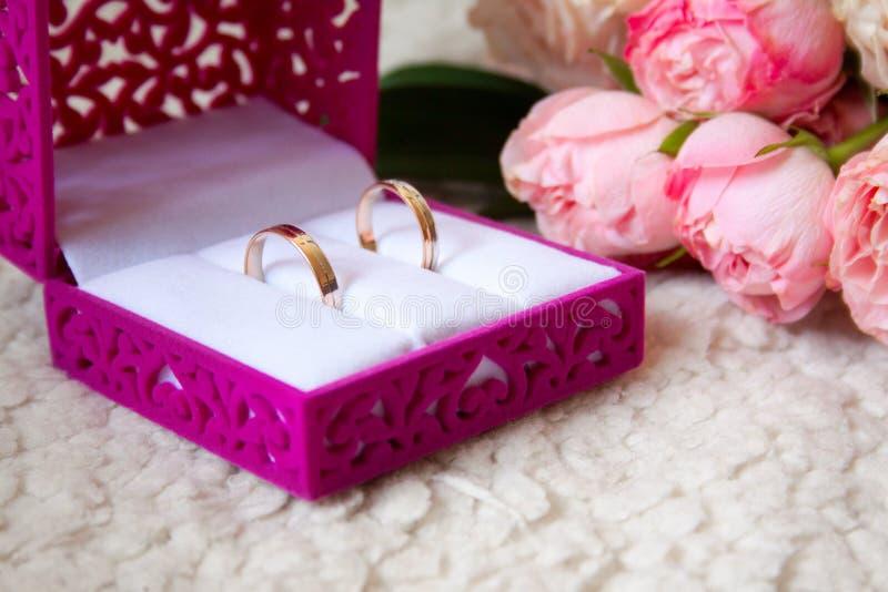 在天鹅绒被雕刻的箱子和婚姻的花束的结婚戒指 库存图片
