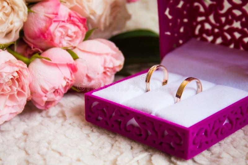 在天鹅绒被雕刻的箱子和玫瑰婚姻的花束的结婚戒指  库存图片