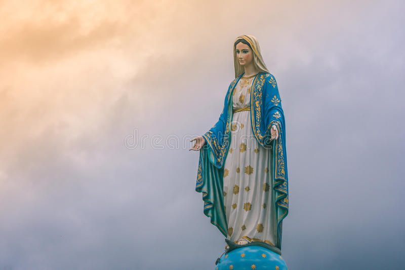 在天主教会的圣母玛丽亚雕象有阳光的在多云天背景中 免版税库存照片