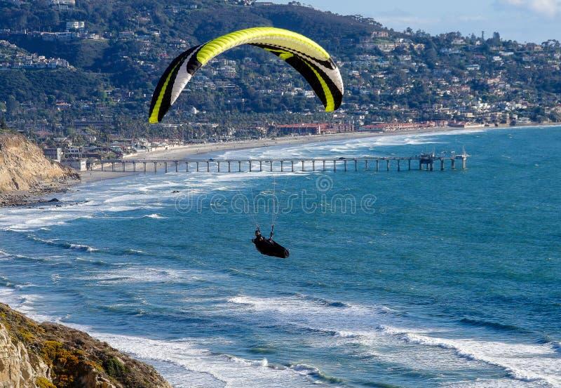 在太平洋上的滑翔伞有海洋学码头的斯克里普斯机关的在背景,拉霍亚,加州中 库存图片