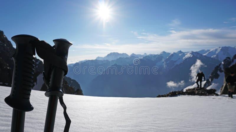 在太阳、多雪的山、天空蔚蓝和云彩的背景的迁徙的杆 图库摄影