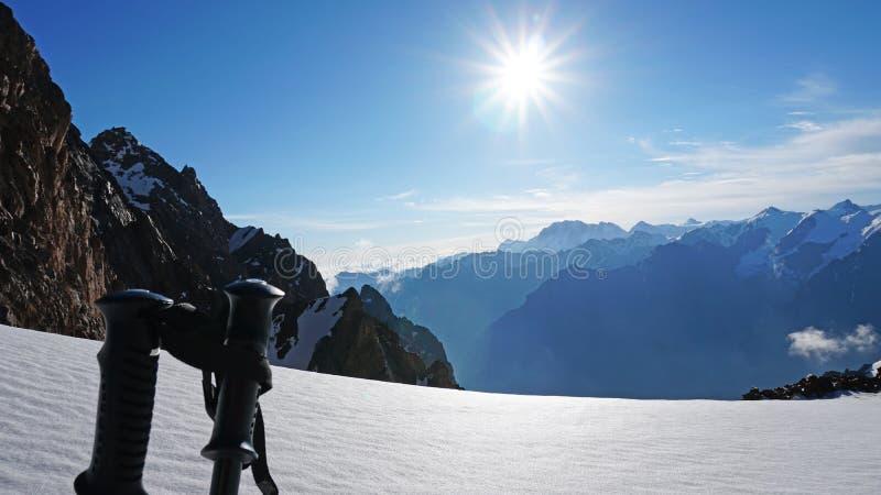 在太阳、多雪的山、天空蔚蓝和云彩的背景的迁徙的杆 库存图片