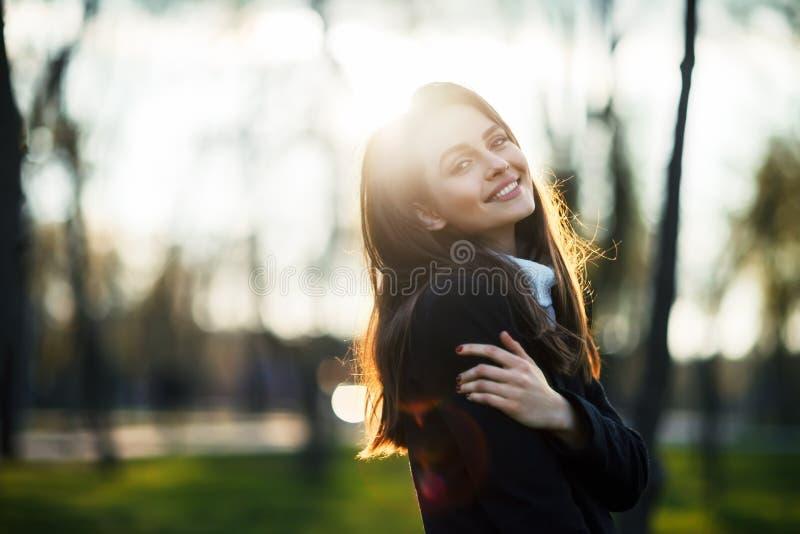 在太阳光的微笑的美丽的妇女画象 免版税库存图片