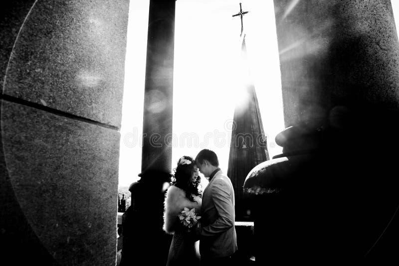 在太阳光芒的夫妇在老哥特式大教堂屋顶的  免版税库存照片