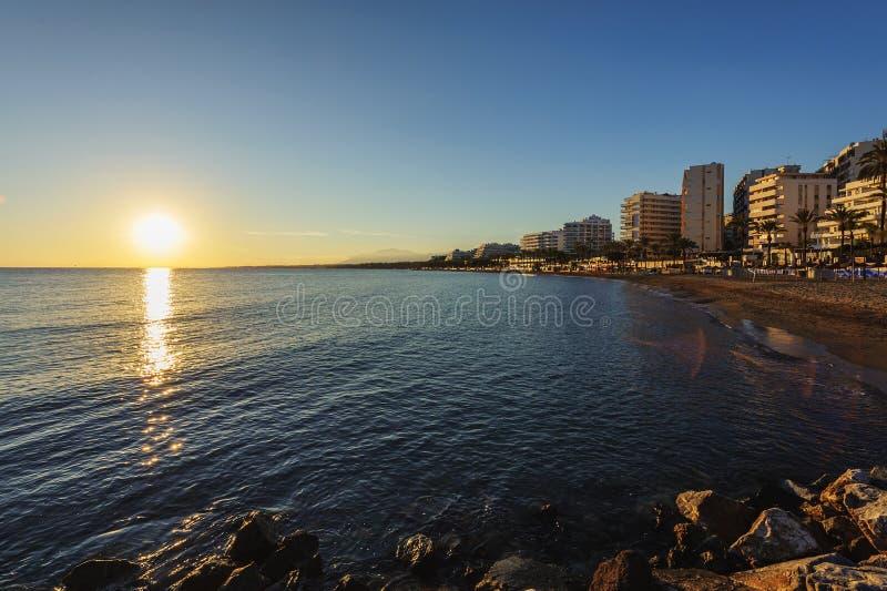 在太阳海岸海滩的日落海岸线在马尔韦利亚镇,安大路西亚,西班牙 免版税库存照片