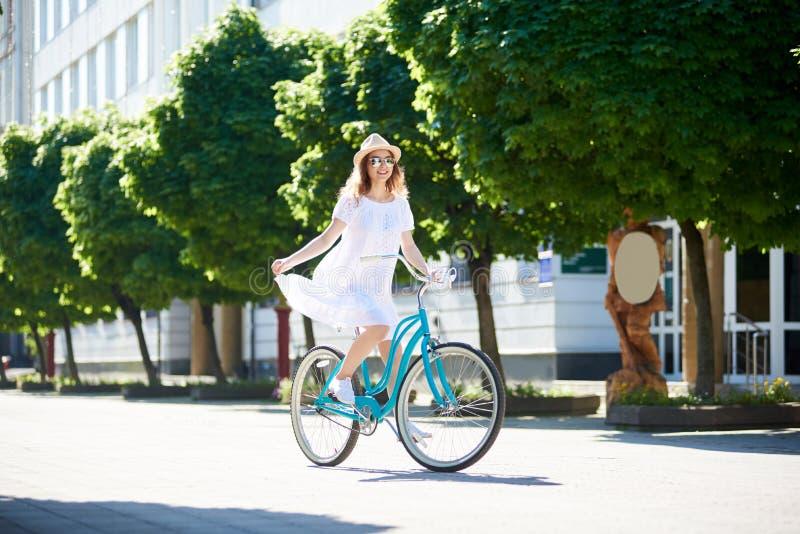 在太阳的晴朗的女孩骑马在蓝色减速火箭的自行车 库存图片