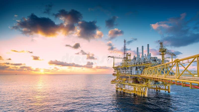 在太阳的近海油和煤气建筑平台被设置导致的原料气体和原油集合的对向着海岸的精炼厂的地方 免版税库存图片