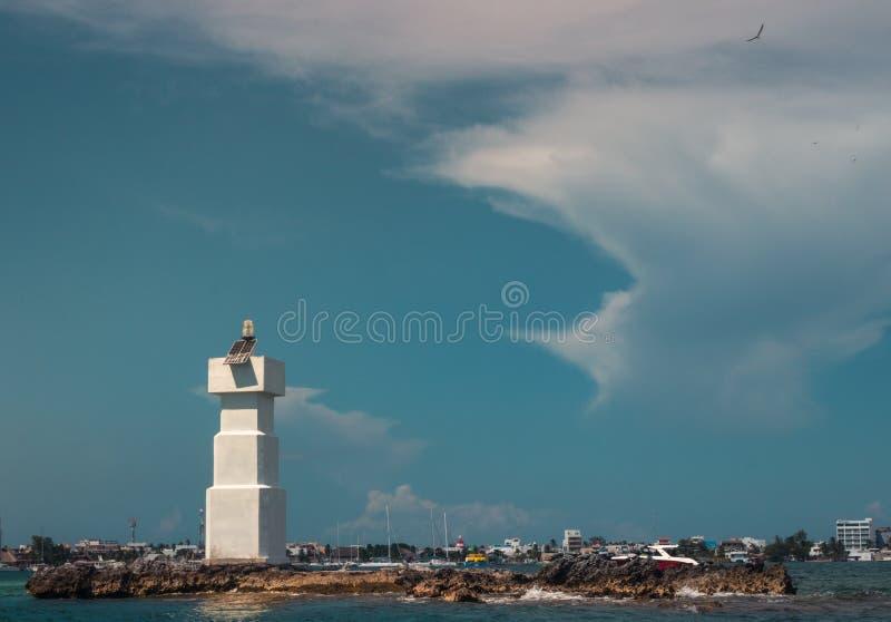 在太阳盖的海的灯塔发出光线 免版税库存照片