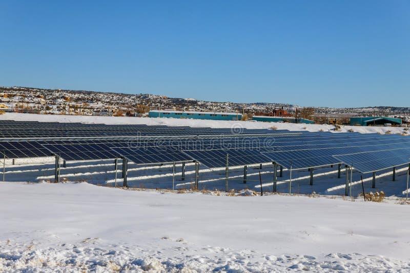 在太阳能驻地的太阳电池板在积雪的山和白色云彩在背景中 免版税库存图片