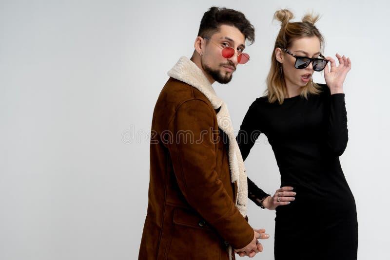 在太阳镜、有胡子的人棕色外套的和白肤金发的女孩的年轻时髦的夫妇摆在反对白色的黑礼服的 库存图片