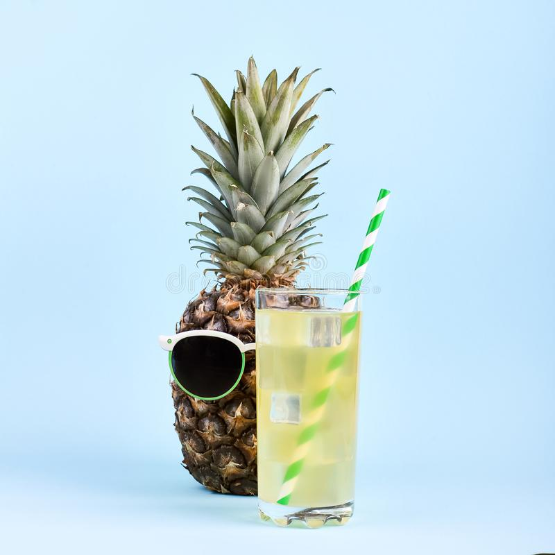 在太阳镜和汁液在玻璃,一种滑稽的夏天心情的概念的菠萝,在蓝色背景 免版税库存图片