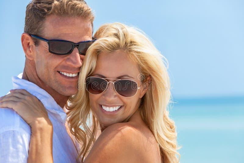 在太阳镜的愉快的有吸引力的妇女和人夫妇在海滩 免版税库存图片