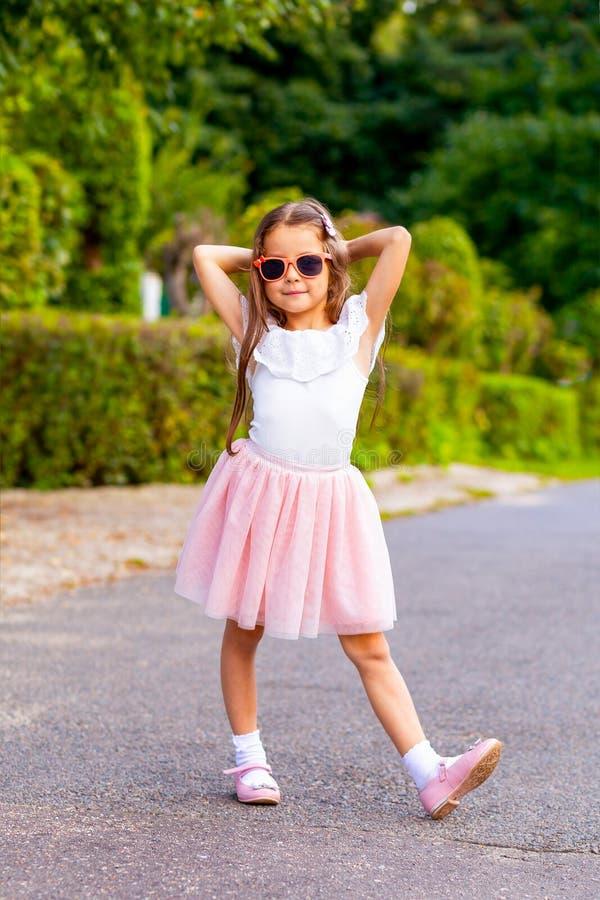 在太阳镜的时兴的小女孩微笑在街道上 Verti 免版税库存图片