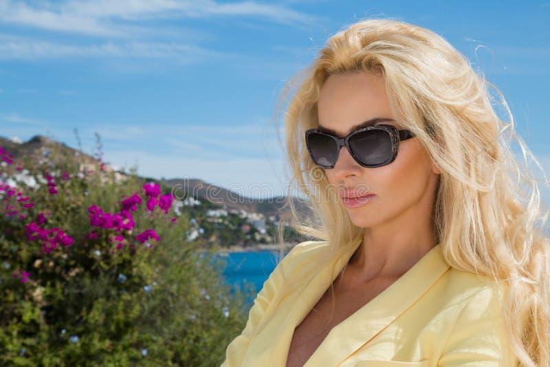 在太阳镜的美好的金发性感的妇女女孩模型在黄色礼服,典雅的夹克 免版税库存照片