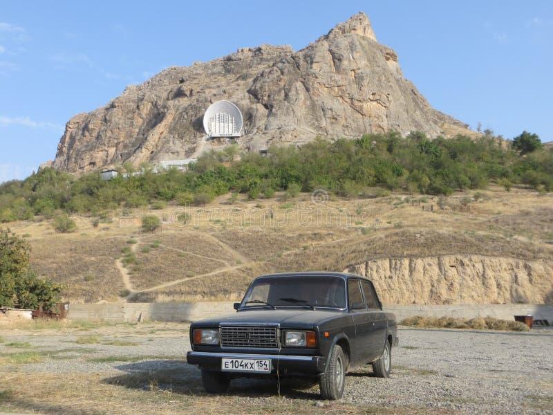 在太Sulaiman山的背景的Lada 2107在奥什 库存图片