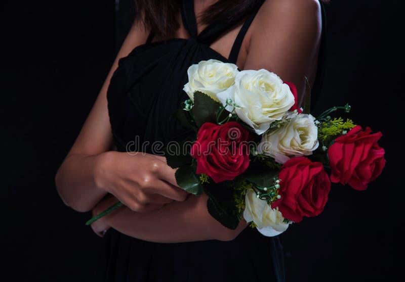 在夫人手,红色和白色玫瑰的特写镜头玫瑰色花束 库存照片