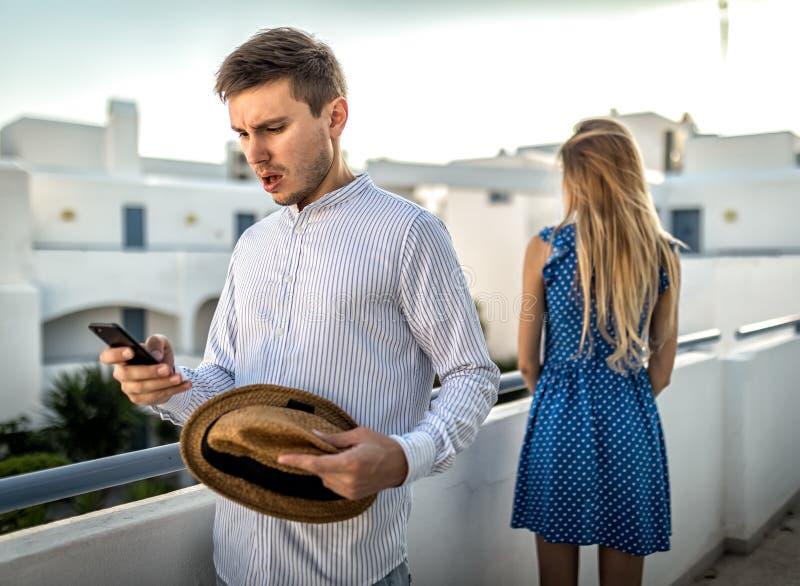 在夫妇丈夫和妻子之间的家庭争吵触犯了室外 在电话谋反背叛的秘密书信 图库摄影