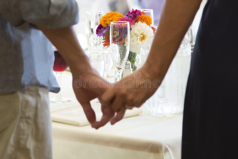 在夫妇构筑的招待会桌上的花握手 免版税库存照片