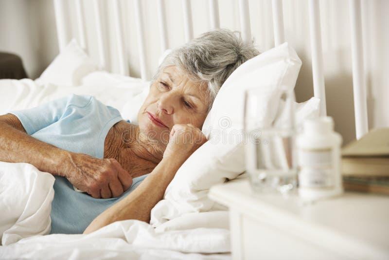 在失眠的资深妇女床头柜上的疗程  库存图片