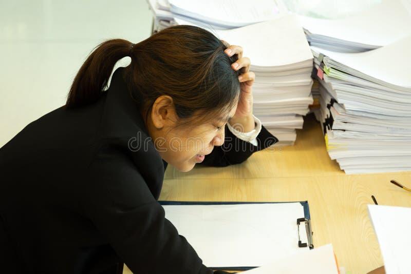 在头的女实业家休息的手有眼睛的接近在工作书桌在办公室 免版税库存图片