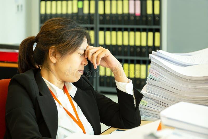 在头的女实业家休息的手有眼睛的接近在工作书桌在办公室 免版税库存照片