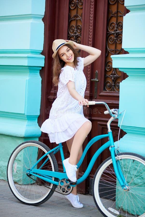 在头饰的模型在葡萄酒自行车摆在反对老大厦 免版税库存图片