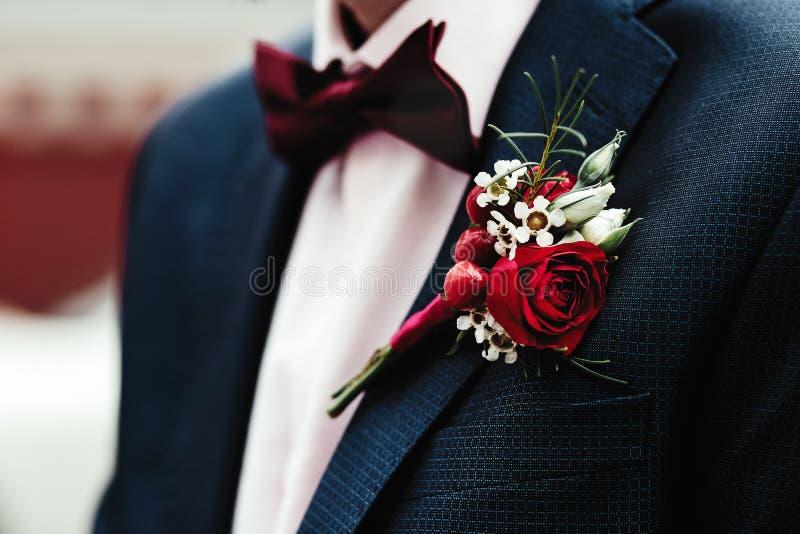 在夹克的新郎的钮扣眼上插的花 免版税图库摄影