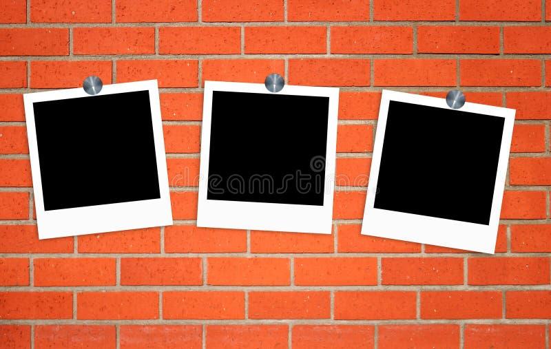 在夹子的空白的老照片在砖墙上 库存图片