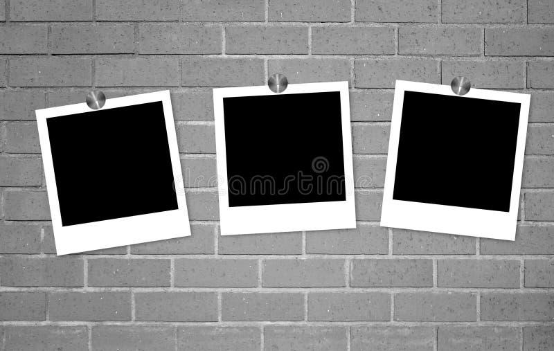 在夹子的空白的老照片在砖墙上 库存照片