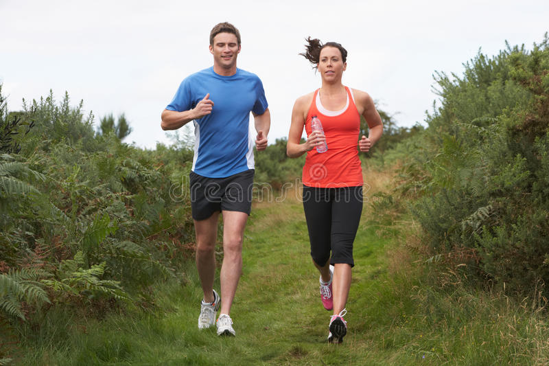 在奔跑的夫妇在乡下 免版税库存图片