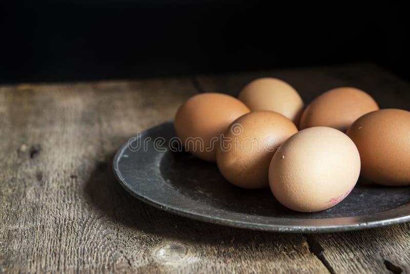 在奖杯板材的新鲜的鸡蛋在葡萄酒减速火箭的样式自然lighti 免版税库存照片