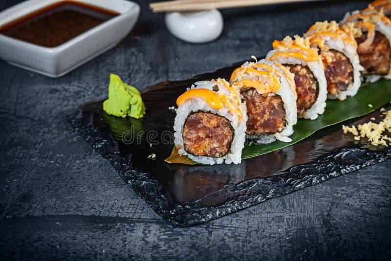 在套的接近的看法寿司卷 与金枪鱼和鱼子酱的辣卷在黑暗的背景的黑石头服务 日本烹调 免版税库存图片
