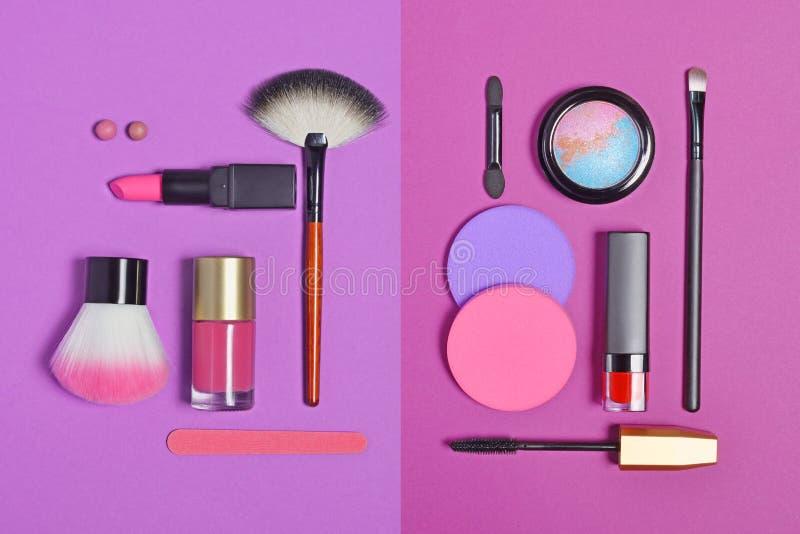 在套的顶视图作为装饰化妆用品的美容品和在明亮的紫色背景的构成刷子 免版税库存照片