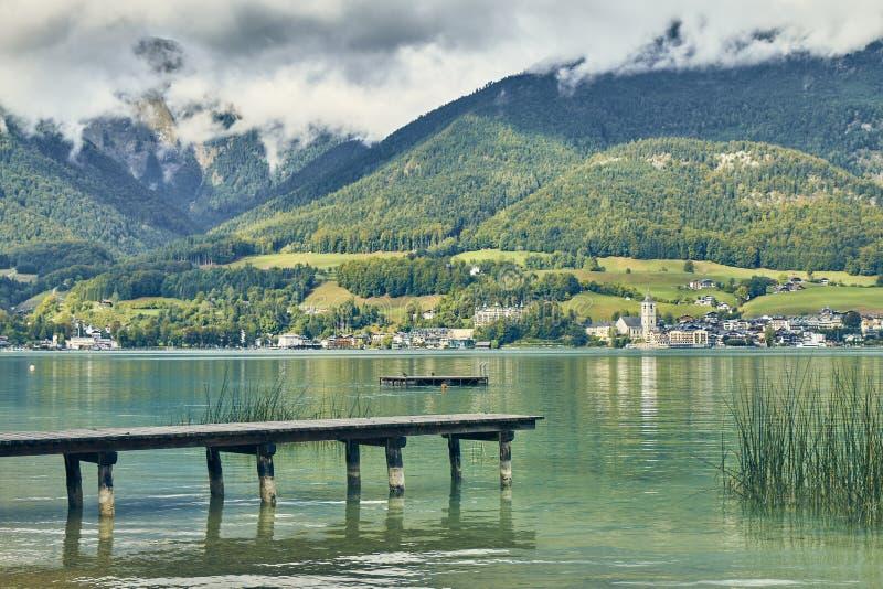 在奥地利使深蓝色的Wolfgangsee湖环境美化看法有一个甲板的从Gschwendt村庄海岸 免版税图库摄影