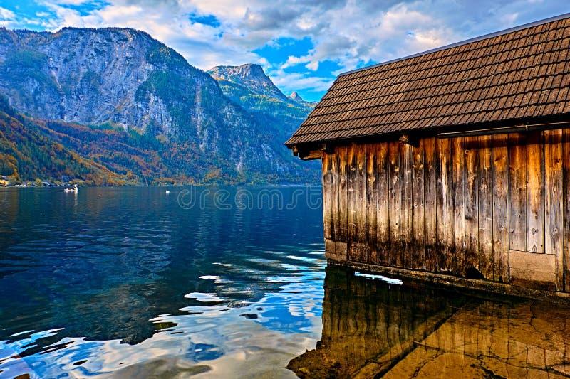 在奥地利阿尔卑斯湖的美好的风景日落 木船库在阿尔卑斯在Hallstatt湖的山村 地点: 图库摄影