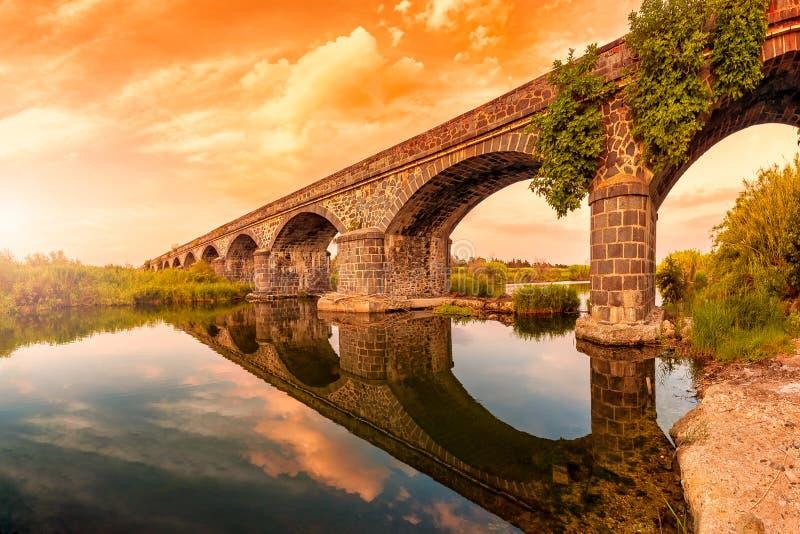 在奥罗塞伊古老桥梁的日落的概要河的Cedrino,撒丁岛 免版税库存图片