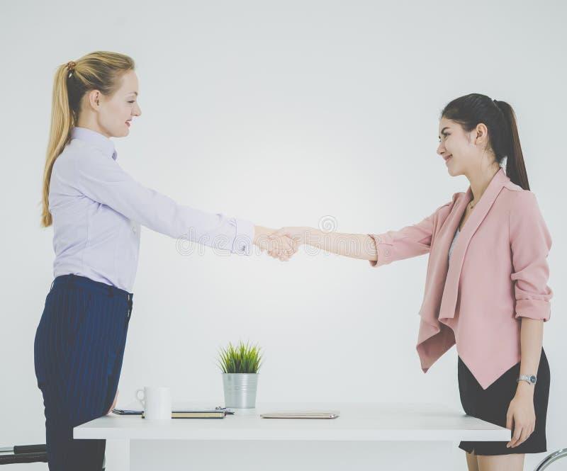 在女商人之间的企业握手在成功成交 库存图片